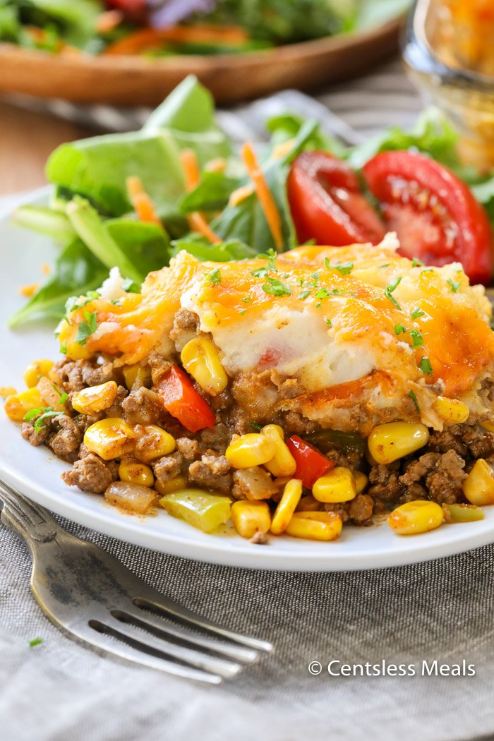 A serving of Taco Shepherd's Pie on a white plate with a side garden salad