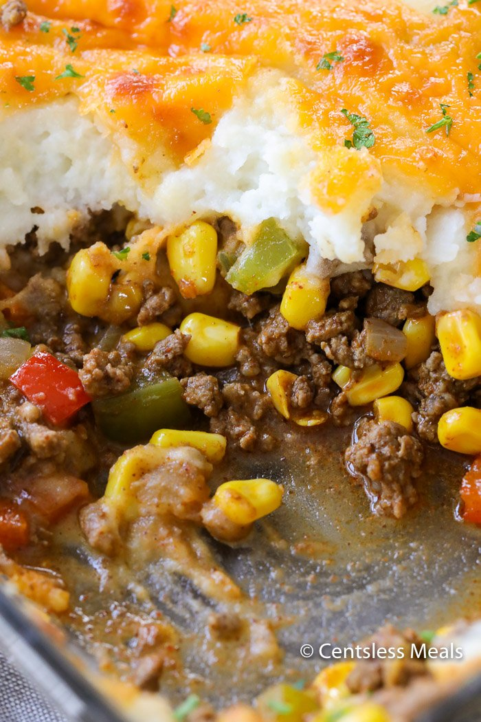 Taco shepherd's pie in a casserole dish with a scoop taken out