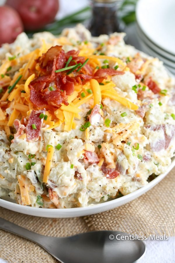 A white bowl of cold laded baked potato salad topped with cheddar cheese, crumbled bacon, and fresh chives.