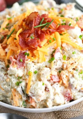 Potato salad in a bowl with bacon and cheese