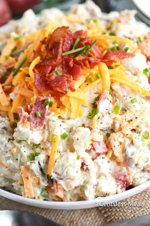 A close up of delicious cold baked potato salad topped with bacon, chives, and crumbled bacon in a white bowl