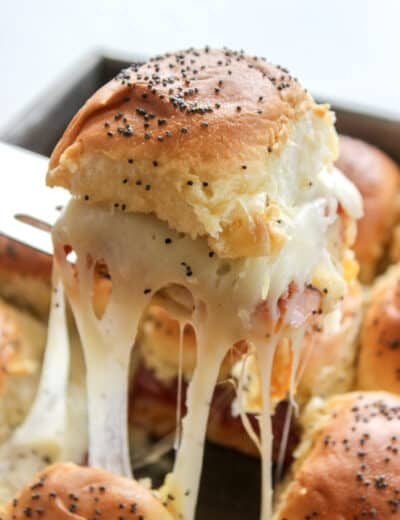Italian Sliders in a pan with one being pulled out to show the melted cheese