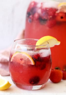 Lemonade in a glass with berries and lemon wedges