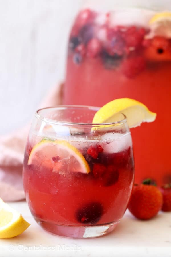 A cup of Sparkling Berry Lemonade with lemons and berries.