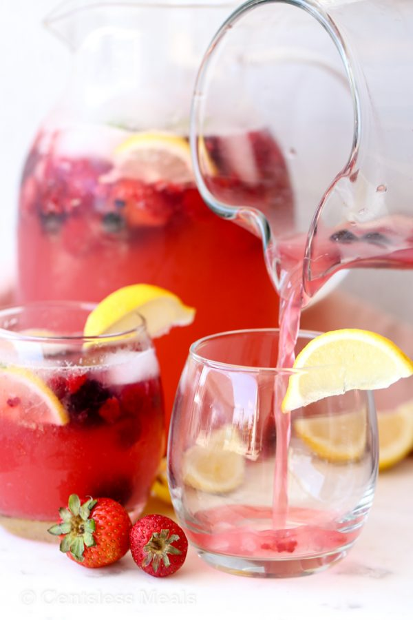 Sparkling Berry Lemonade being poured into a glass from a pitcher.