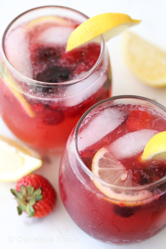 Two glasses of Sparkling Berry Lemonade with berries and lemon slices.