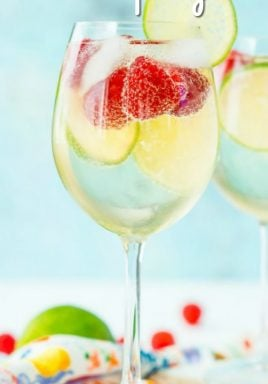 Raspberry Lime Wine Spritzer is a simple and refreshing cocktail that requires just 4 ingredients and a few minutes to make! #centslessmeals #winespritzer #easyrecipe #easydrink #simplerecipe #withfruit #withclubsoda #summerdrink #partydrink #fundrink #foracrowd #dinnerparty