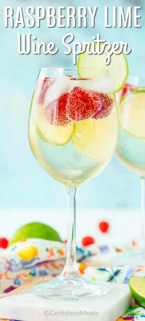 Raspberry lime wine spritzer in a wine glass with a title