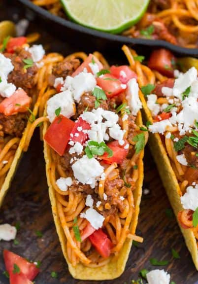 Spaghetti Tacos are messy, fun and extra delicious. Cooked in a rich beef and tomato sauce and served in crispy taco shells with your favorite toppings.