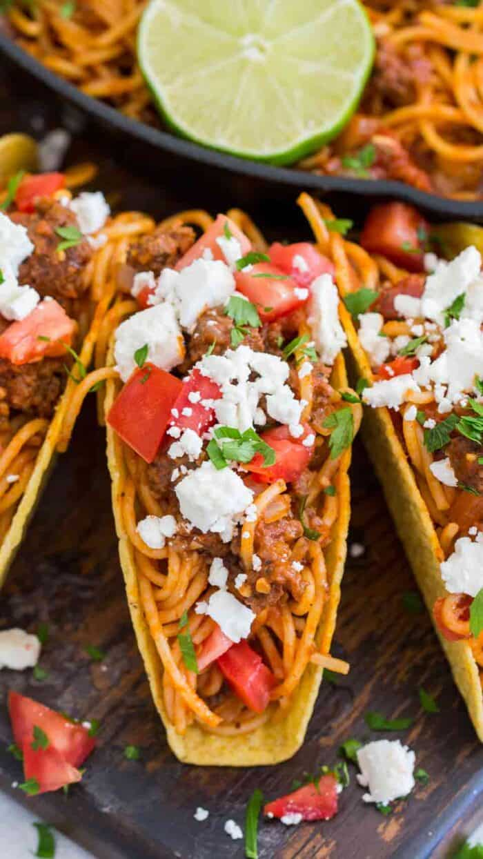 Spaghetti Tacos in crispy taco shells and topped with cheese and tomatoes