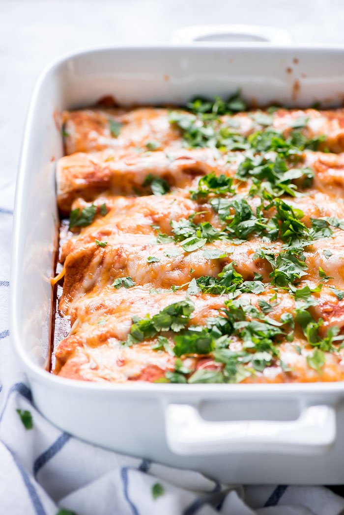 Easy Beef Enchiladas in a white 9x13 inch baking dish topped with melted cheese and cilantro.