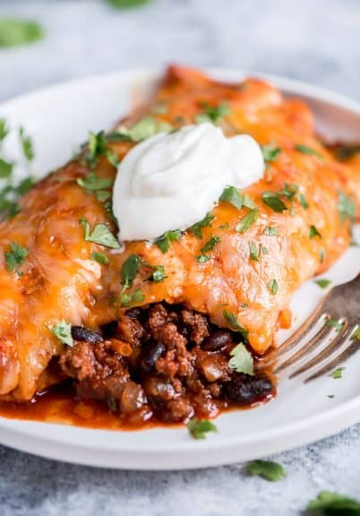 Beef enchiladas on a white plate with a dollop of sour cream