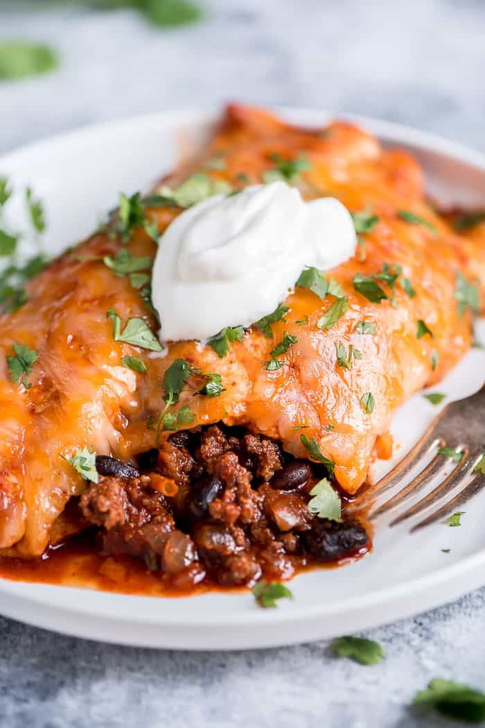 Beef Enchiladas topped with cilantro and sour cream and served on a white plate.