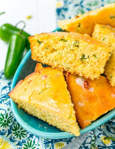 Jalapeno cornbread in a blue bowl with jalapenos on the side