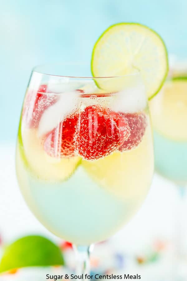 Raspberry Lime Wine Spritzer with a lime wedge garnish on the glass