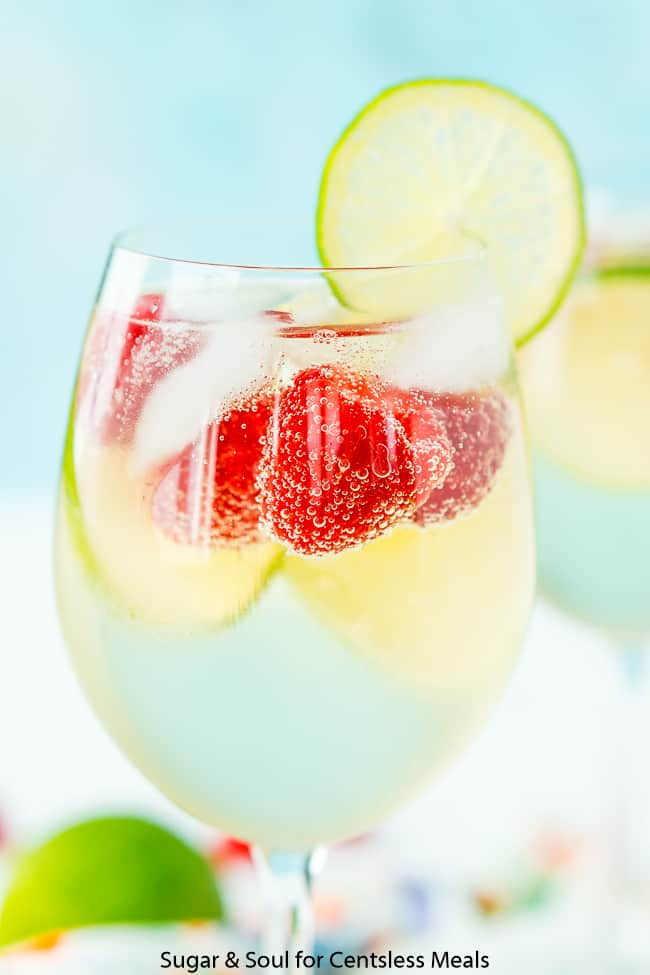 Raspberry lime wine spritzer with berries and lime as garnish