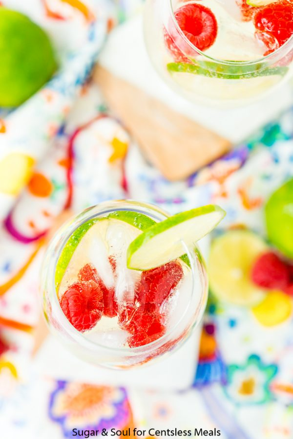 A top view of two glasses of Raspberry Lime Wine Spritzer on a colorful tablecloth