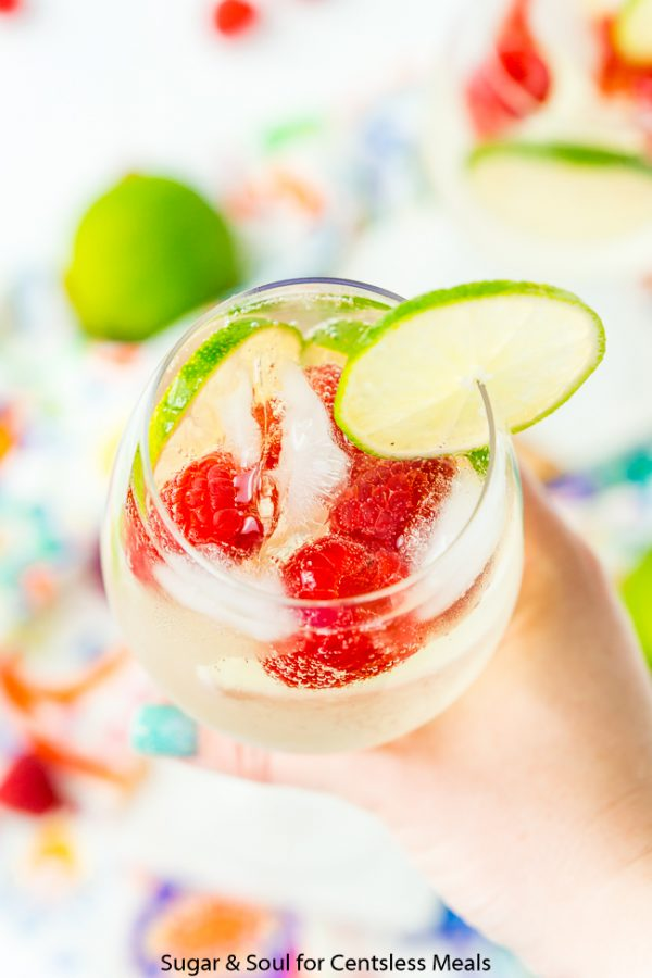 Raspberry lime wine spritzer in a glass with a lime slice