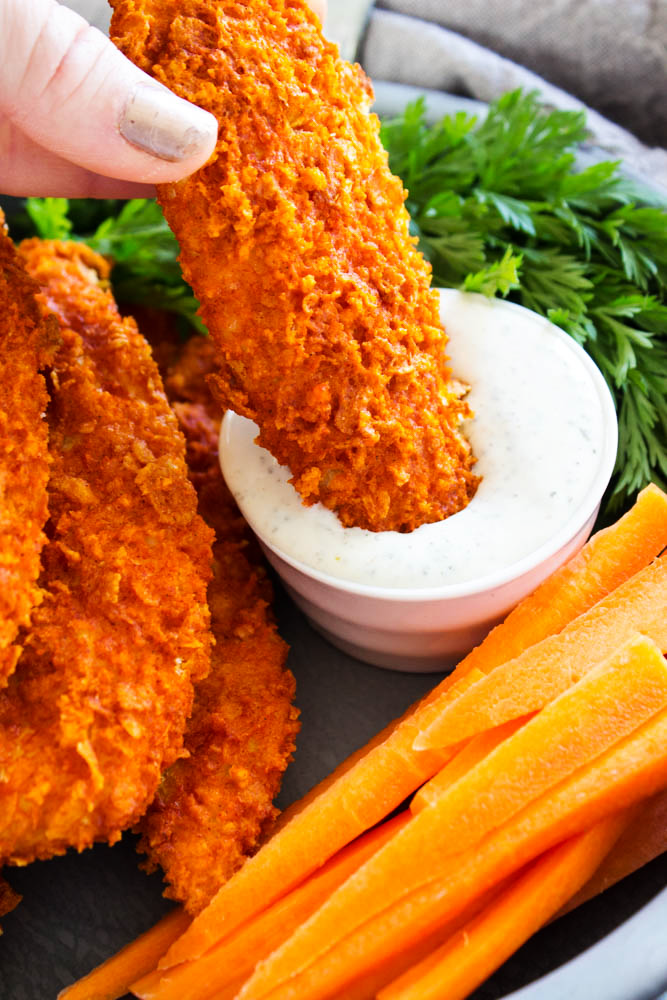 Baked Buffalo Chicken Tenders dipped in dipping sauce