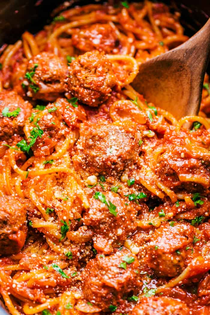 spaghetti and meatballs in a crock pot with a spoon