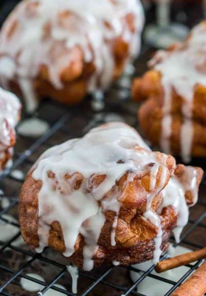 Apple fritters with icing and cinnamon sticks