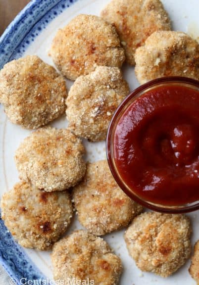 Homemade chicken nuggets on a plate with a bowl of ketchup