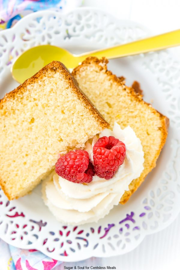 Overhead picture of Almond Pound Cake on a white plate and garnished with whipped cream and berries