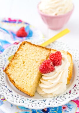 Almond pound cake on a white plate with icing and raspberries