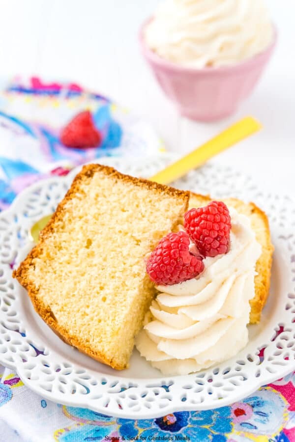 Almond Pound Cake served on a white plate with whipped cream and raspberries