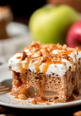 Caramel apple poke cake drizzled with caramel on a white plate