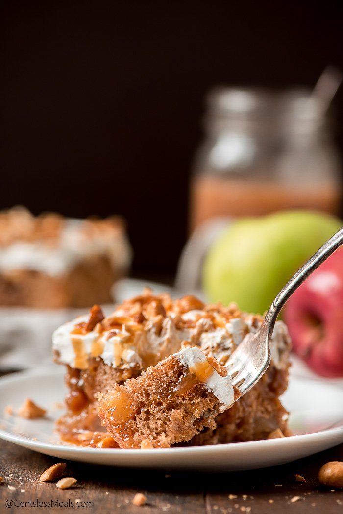 A fork full of Caramel Apple Poke Cake ready to eat.
