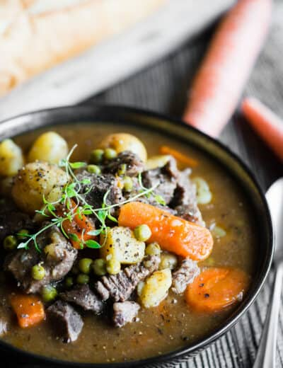 instant pot beef stew in a bowl garnished with thyme