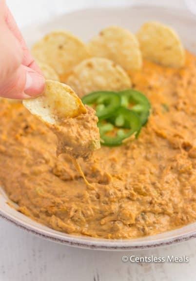 Chili cheese dip in a bowl with some being dipped onto a chip
