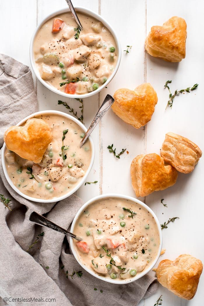 Three bowls of chicken pot pie soup and heart puff pastries scattered on the table.