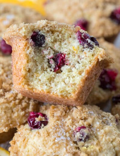Cranberry orange muffins with a bite taken out of one to show the inside