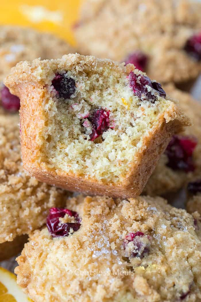 Cranberry orange muffins piled in a dish with a bite taken out of one.