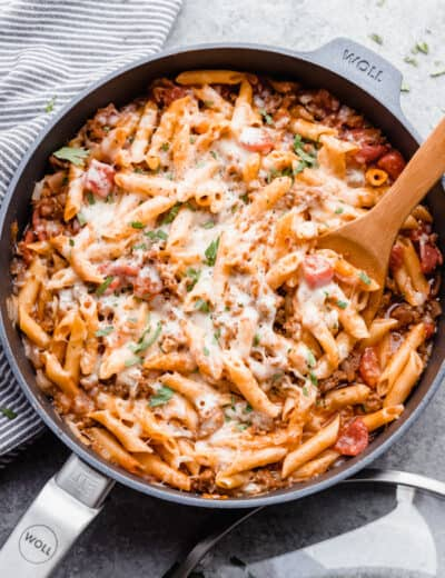 Italian sausage pasta being served out of a skillet.