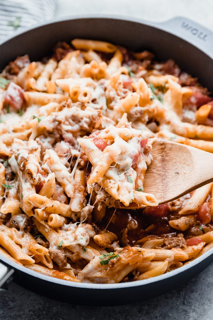Italian sausage pasta in a skillet with melted cheese being served with a wooden spoon.