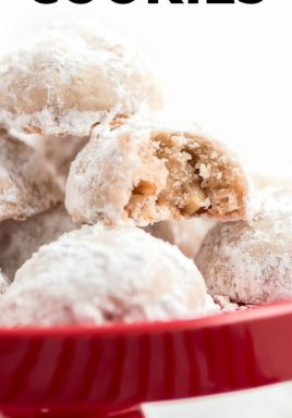 Snowball cookies on a red plate with a bite taken out of one and a title