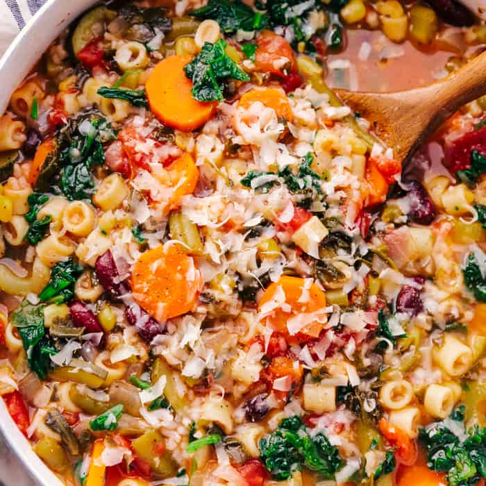 Minestrone soup in a bowl with a wooden spoon