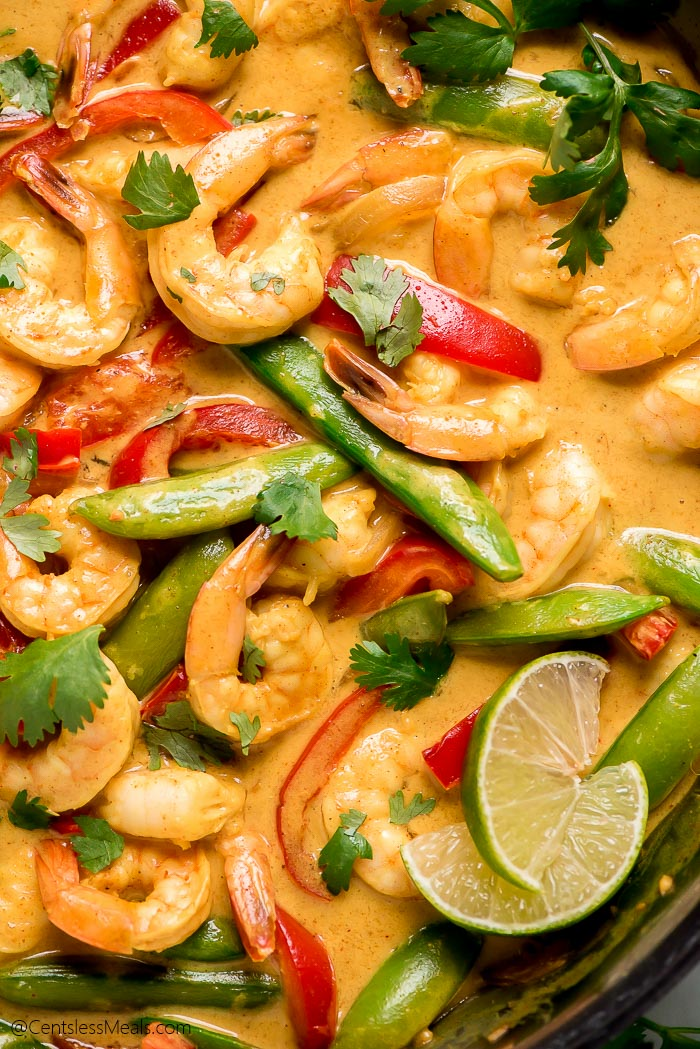 Close up of Shrimp Curry in a pan showing the creamy sauce, shrimp, red peppers, and sugar snap peas.
