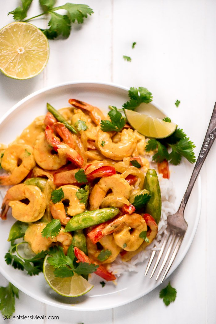 A plate full of Shrimp Curry on a bed of rice and garnished with cilantro and lime wedges.
