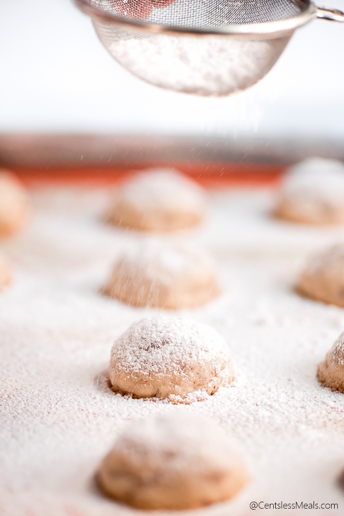 Sifting powdered sugar over the top of Snowball Cookies on a baking sheet.