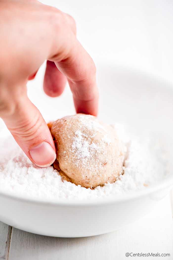 Snowball cookies being dipped in powdered sugar