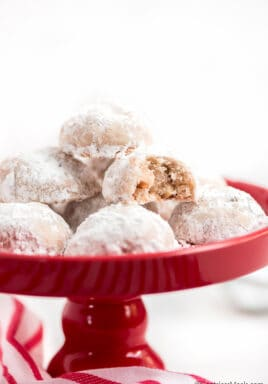 Snowball cookies on a red plate with a bite taken out of 1