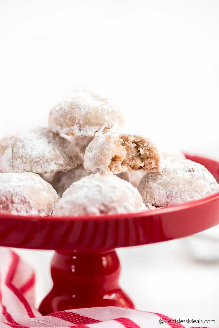 Snowball Cookies stacked on a cake stand with a bite taken out of one showing the pecans inside.