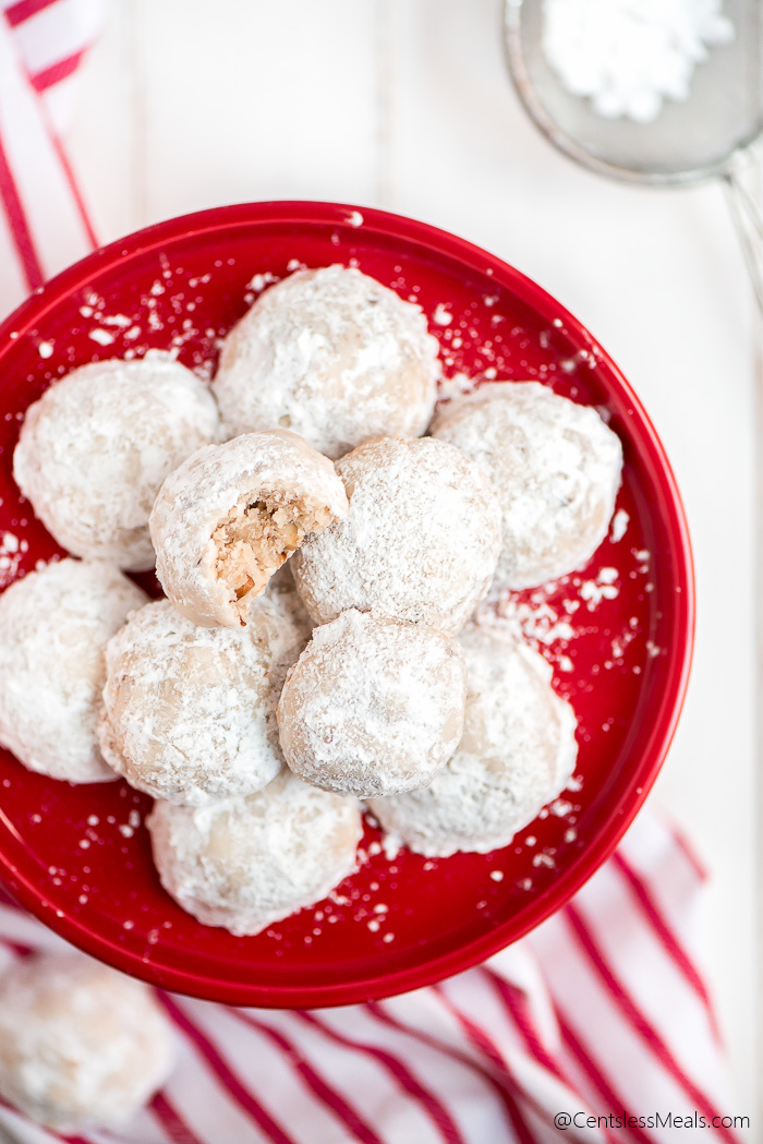 Top view of Snowball Cookies on a red cake stand with powdered sugar spread around. One cookie has a bite taken out, showing the pecans inside.