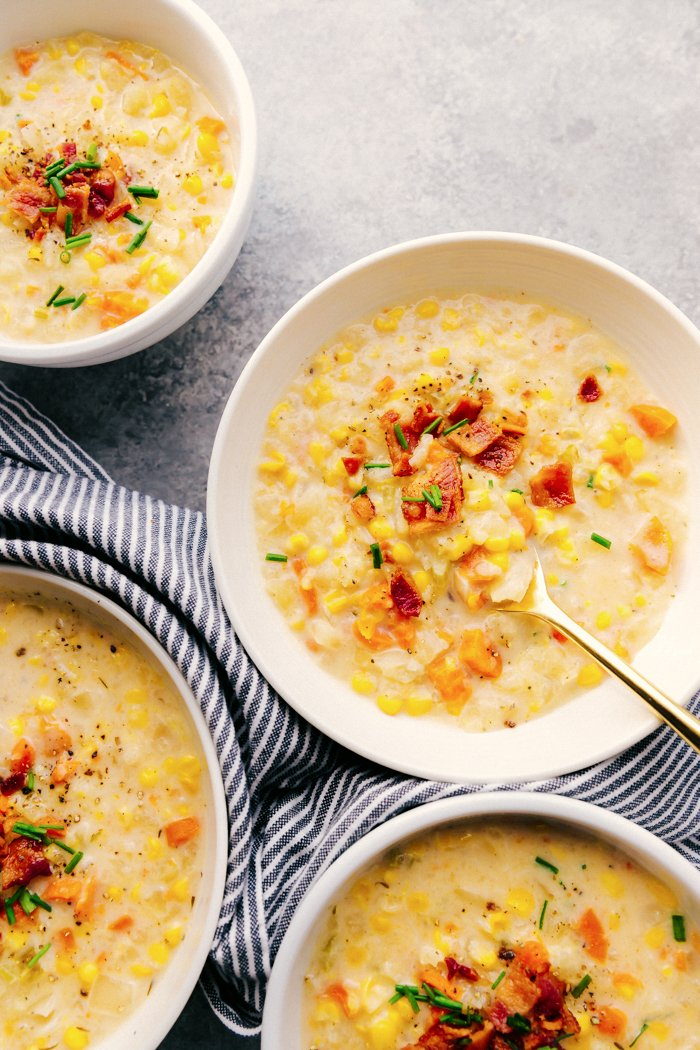 Crock-Pot corn chowder in white bowls garnished with bacon and chives