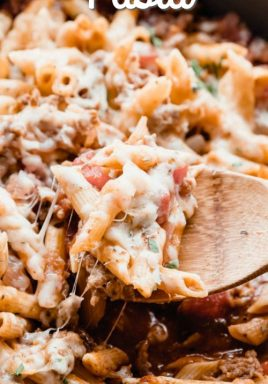 Italian sausage pasta in a pan with a wooden spoon and a title