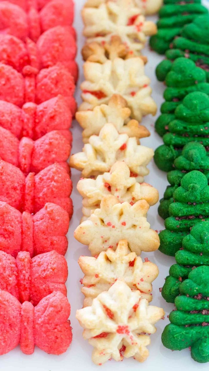 Spritz Cookies lined up in three rows with each row being a different shape and color